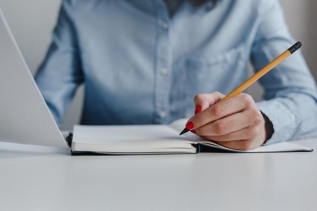 Primer plano de la mano de una mujer con uñas rojas escribiendo en un cuaderno con un lápiz amarillo y sosteniendo documentos con camisa azul