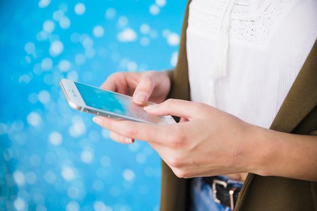 Primer plano de la mano de la mujer con smartphone