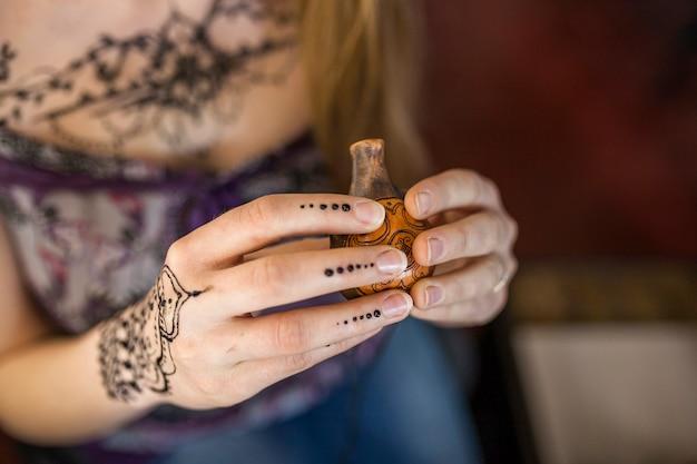 Primer plano de la mano de la mujer sosteniendo el antiguo recipiente de madera