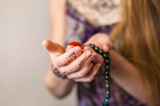 Primer plano de la mano de una mujer sosteniendo bolas chinas rojas y cuentas espirituales
