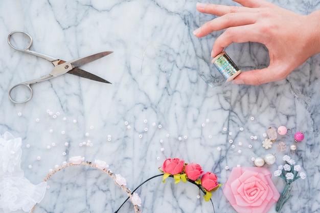 Primer plano de la mano de una mujer sosteniendo un carrete de plata tijera; rosario; cinta rosa y diadema en mármol con textura telón de fondo