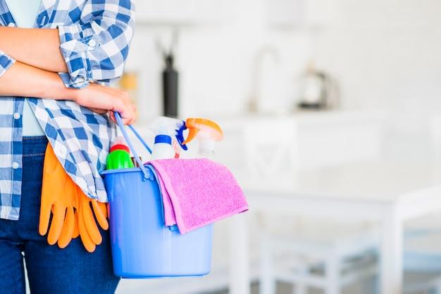 Primer plano de la mano de la mujer sosteniendo el cubo con productos de limpieza y servilleta rosa