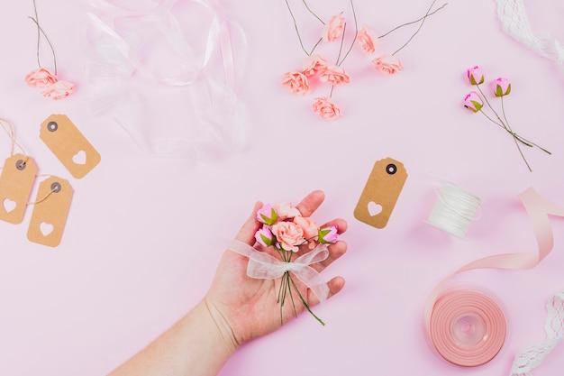 Primer plano de la mano de una mujer sosteniendo una flor atada con una cinta blanca sobre un fondo rosa