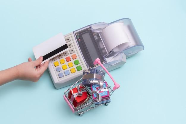 Primer plano de la mano de una mujer sosteniendo una tarjeta bancaria sobre la caja registradora para pagar una compra en una tienda y un carrito pequeño con cajas de regalo, vista superior, espacio de copia. concepto de negocio