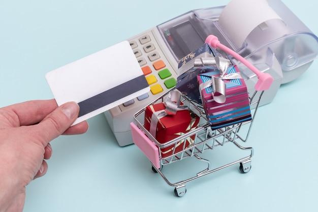 Primer plano de la mano de una mujer sosteniendo una tarjeta bancaria sobre una terminal de caja registradora para pagar las compras en un carrito con cajas de regalo, vista lateral, espacio de copia. concepto de negocio. concepto de compras en línea