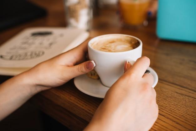 Primer plano de la mano de la mujer sosteniendo la taza de café en la mesa