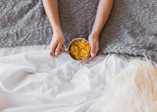 Primer plano de la mano de una mujer sosteniendo un tazón de copos de maíz sobre la alfombra y la manta blanca