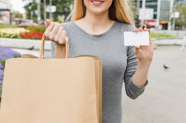 Primer plano de la mano de una mujer con tarjeta de compras y tarjeta blanca en blanco