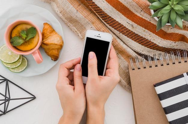 Primer plano de la mano de una mujer mediante teléfono móvil con desayuno y té de limón sobre fondo blanco