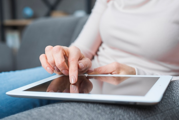 Primer plano de la mano de la mujer tocando la pantalla digital moderna con el dedo