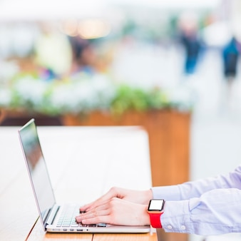 Primer plano de la mano de una mujer usando una computadora portátil sobre un escritorio de madera