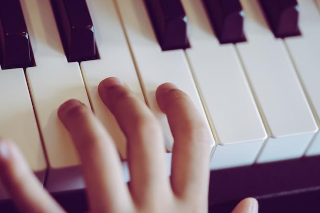 Primer plano de una mano musical para niños tocando el piano.