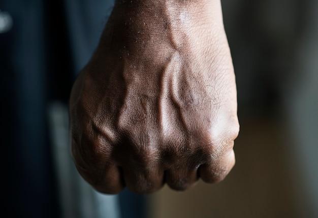 Primer plano de una mano negra en puño