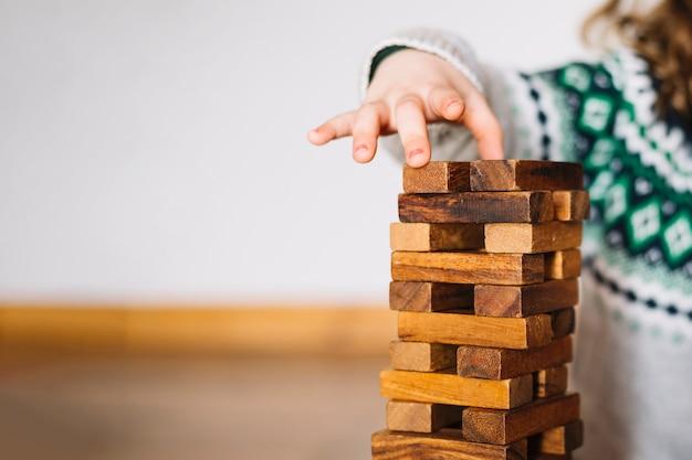 Primer plano de una mano de niña apilando bloques de madera