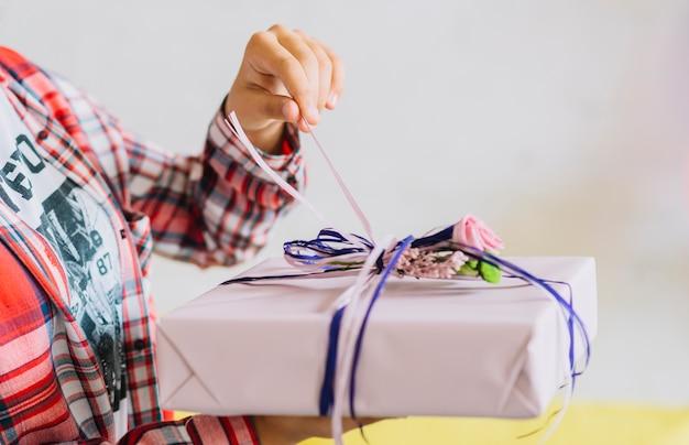Primer plano de la mano de una niña desenvolver el regalo de cumpleaños
