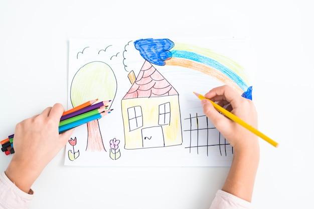 Primer plano de la mano de la niña dibujando la casa con lápiz de color sobre papel con fondo blanco