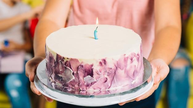Primer plano de la mano de una niña con pastel de cumpleaños