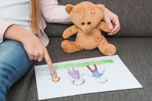 Primer plano de la mano de una niña que muestra un dibujo familiar hecho por ella para un osito de peluche en el sofá