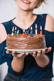 Primer plano de la mano de la niña sosteniendo el plato de pastel de chocolate con velas encendidas