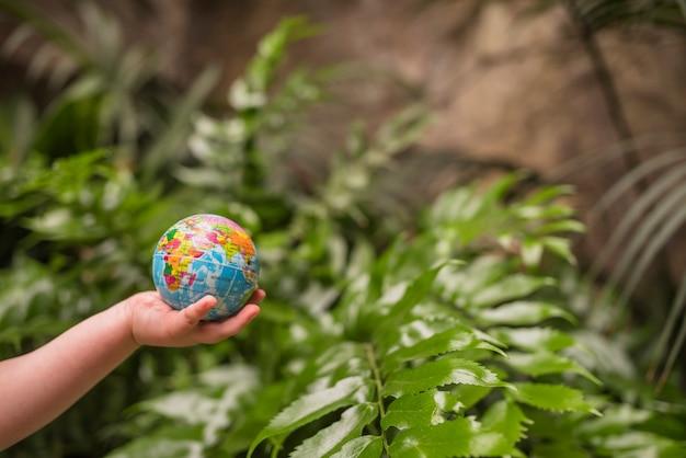 Primer plano de la mano del niño que sostiene la bola del globo inflable