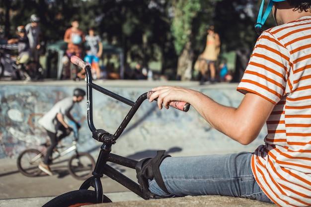 Primer plano de la mano del niño que sostiene la manija de la bicicleta en el parque