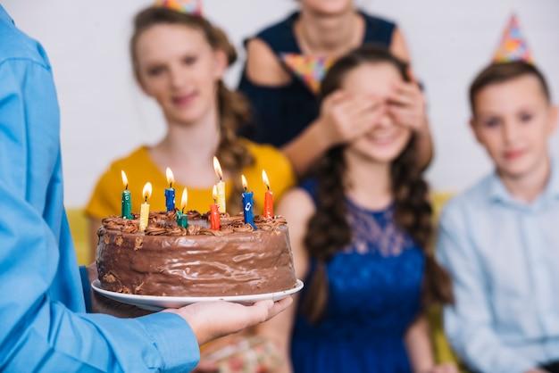Primer plano de la mano de un niño que trae pastel de chocolate a la cumpleañera con los ojos cubiertos por su amiga