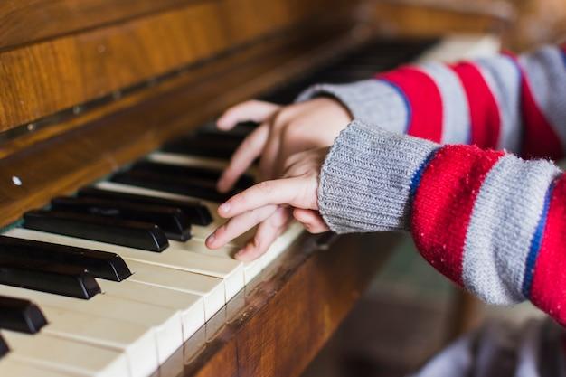 Primer plano de la mano de los niños tocando las teclas del piano
