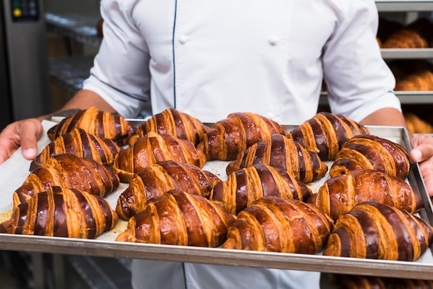 Primer plano de la mano de un panadero masculino que sostiene una bandeja de croissant recién horneada
