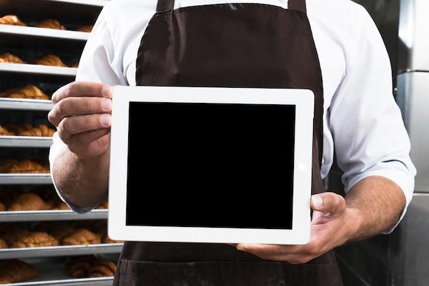 Primer plano de la mano de un panadero masculino que sostiene la tableta digital de pantalla negra