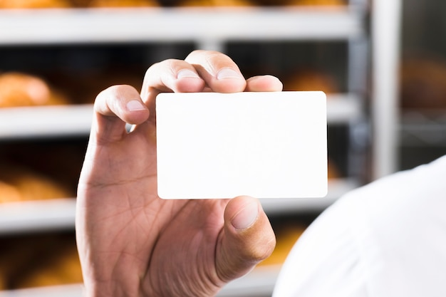 Primer plano de la mano del panadero masculino que sostiene la tarjeta de visita blanca en blanco