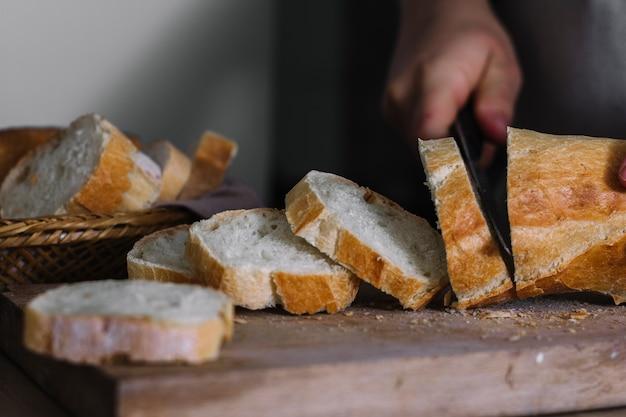 Primer plano de la mano de un panadero que corta pan de pan fresco