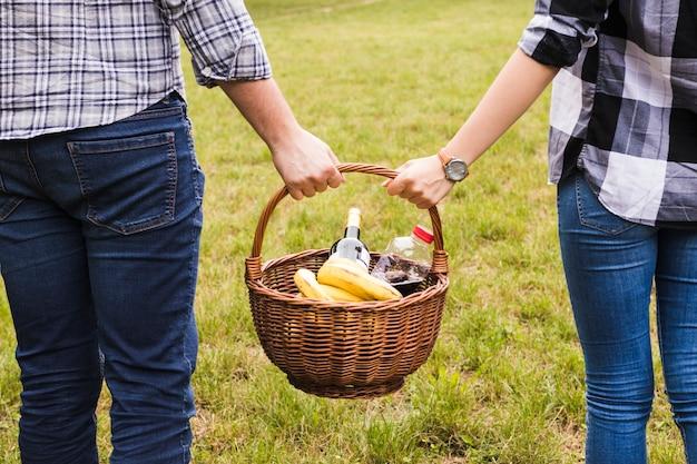 Primer plano de la mano de la pareja sosteniendo la cesta de picnic en el parque