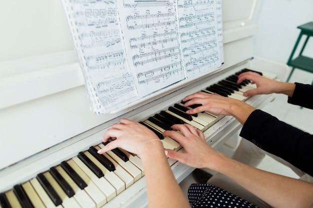 Primer plano de la mano de la pareja tocando el piano con la hoja musical