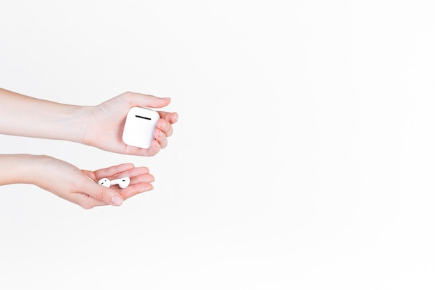 Primer plano de la mano de una persona con audífono y batería
