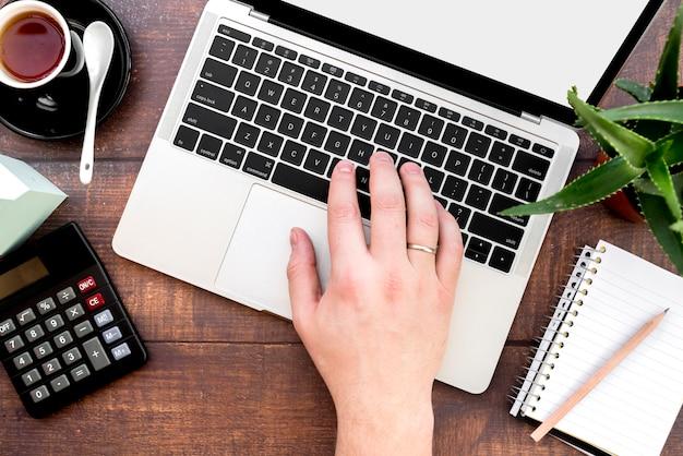Primer plano de la mano de una persona escribiendo en la computadora portátil con la calculadora; taza de café y cuaderno de espiral con lápiz en el escritorio de madera