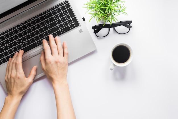 Primer plano de la mano de una persona escribiendo en la computadora portátil con una taza de café; anteojos y planta de maceta en el escritorio blanco