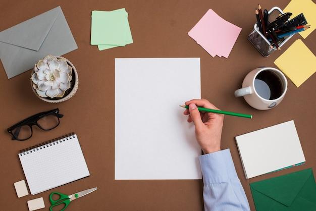 Primer plano de la mano de una persona escribiendo en papel blanco en blanco con papelería en el escritorio