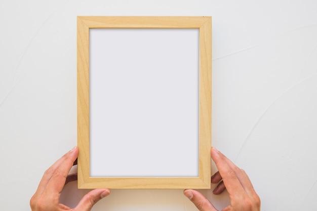 Primer plano de la mano de una persona con marco de madera blanco en la pared