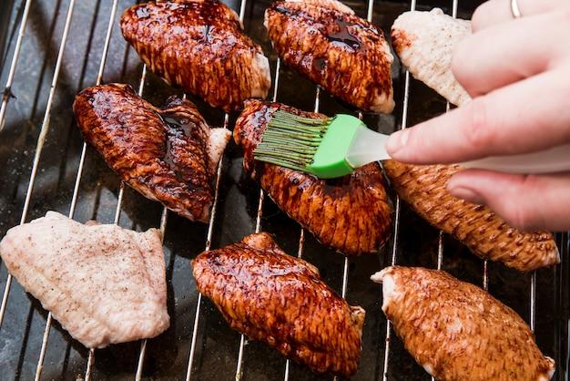 Primer plano de la mano de una persona que aplica aceite a las alitas de pollo asadas con cepillo