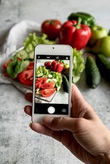 Primer plano de la mano de la persona que captura una fotografía en un teléfono móvil