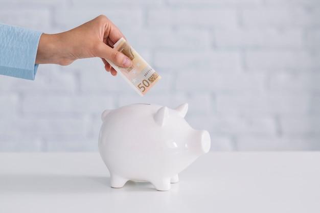 Primer plano de la mano de una persona que inserta billetes de cincuenta euros en piggybank en el escritorio
