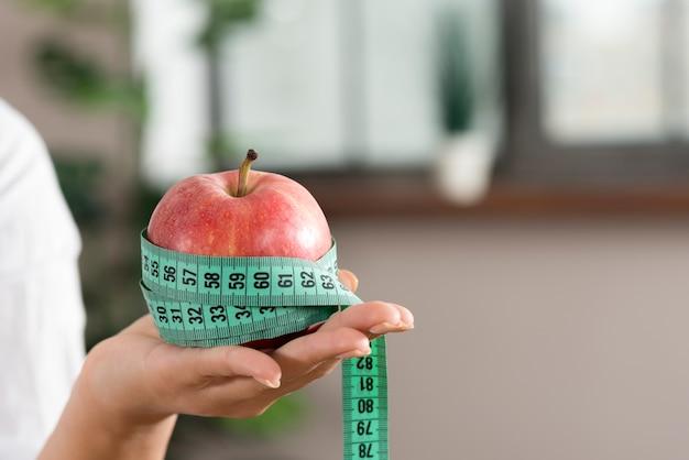 Primer plano de la mano de una persona que muestra una manzana roja con una cinta de medición verde