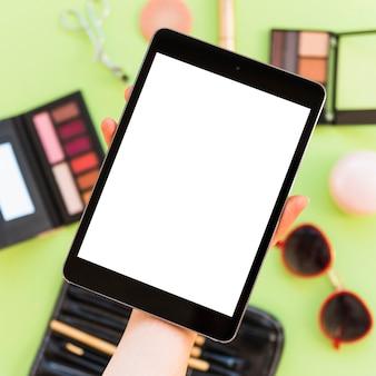 Primer plano de la mano de una persona que muestra la pantalla de la tableta digital en blanco sobre los cosméticos