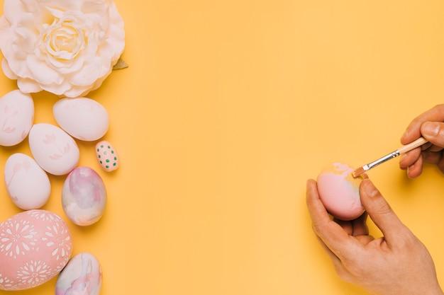 Primer plano de la mano de una persona que pinta el huevo con pincel sobre fondo amarillo