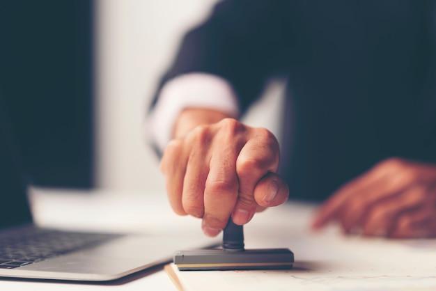 Primer plano de la mano de una persona que sella con el sello aprobado en el documento en el escritorio