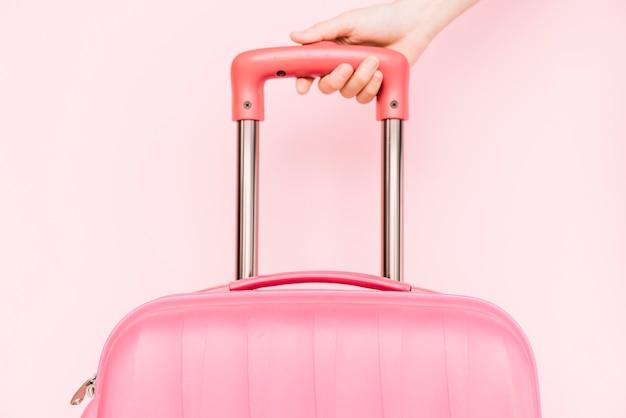 Primer plano de la mano de una persona que sostiene el asa del equipaje de viaje contra un fondo rosa