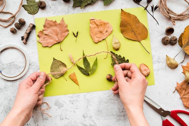 Primer plano de la mano de la persona que sostiene una cuerda sobre las hojas de otoño en un papel verde sobre un fondo texturizado