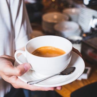 Primer plano de la mano de la persona que sostiene la deliciosa taza de café