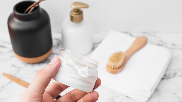 Primer plano de la mano de una persona que sostiene el frasco de crema hidratante
