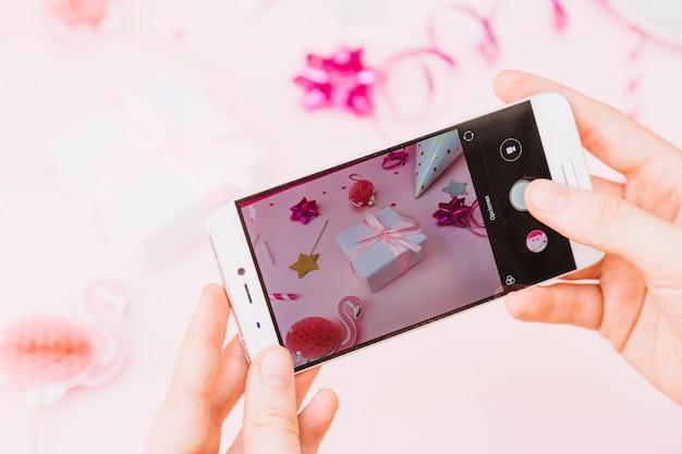 Primer plano de la mano de una persona que toma una foto de los regalos de cumpleaños y la decoración en un teléfono inteligente